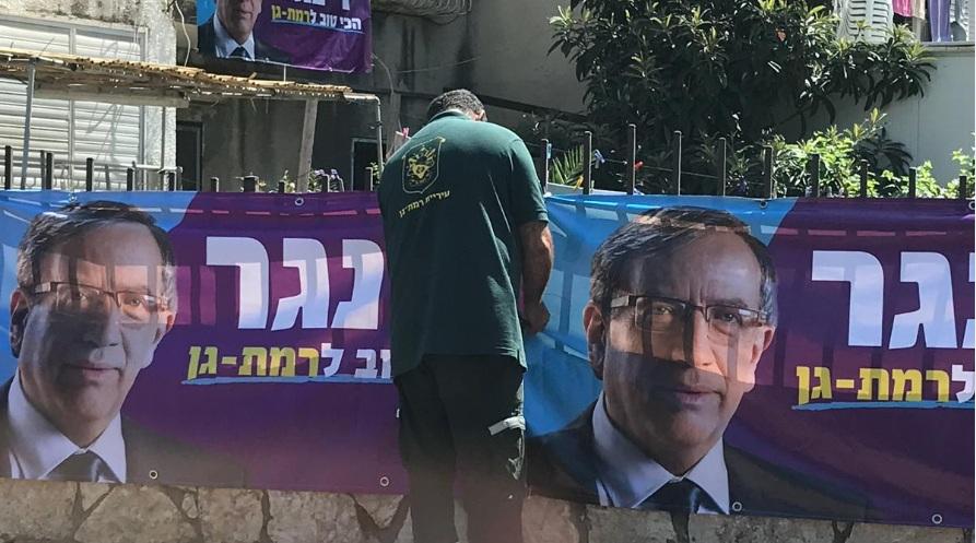 """Photo of צפו: עובד עיריית רמת גן עם חולצה של שפ""""ע תולה שלטים של ישראל זינגר, בניגוד למותר. אז איך מסבירים את זה במטה זינגר?"""