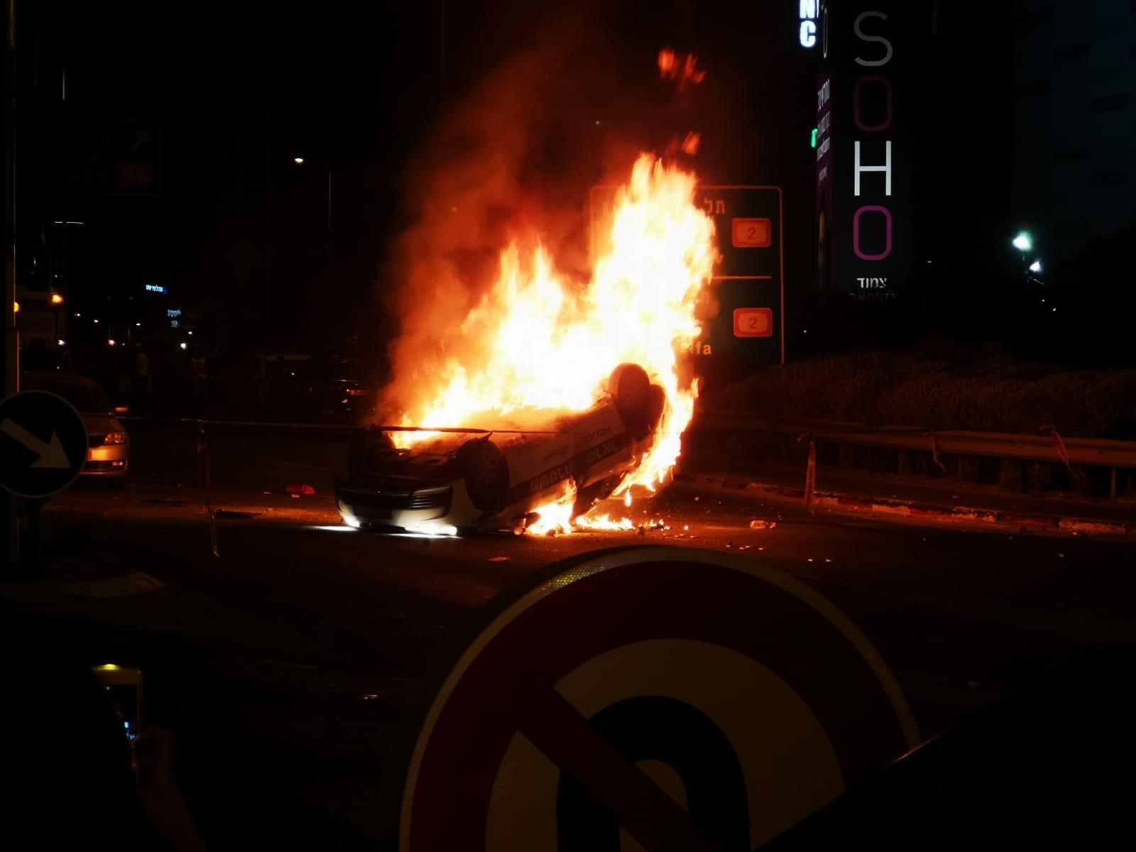 ניידת משטרה עולה באש ומוצתת. צילום: דוברות המשטרה