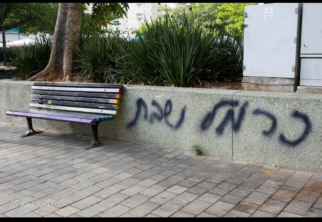 "Photo of גרפיטי נגד כרמל שאמה ליד ספסל במרום נווה, שנצבע בצבעי הגאווה והושחת: ""גרפיטי ופשע שנאה לא ירפו את ידינו מלהיות עיר סובלנית"""