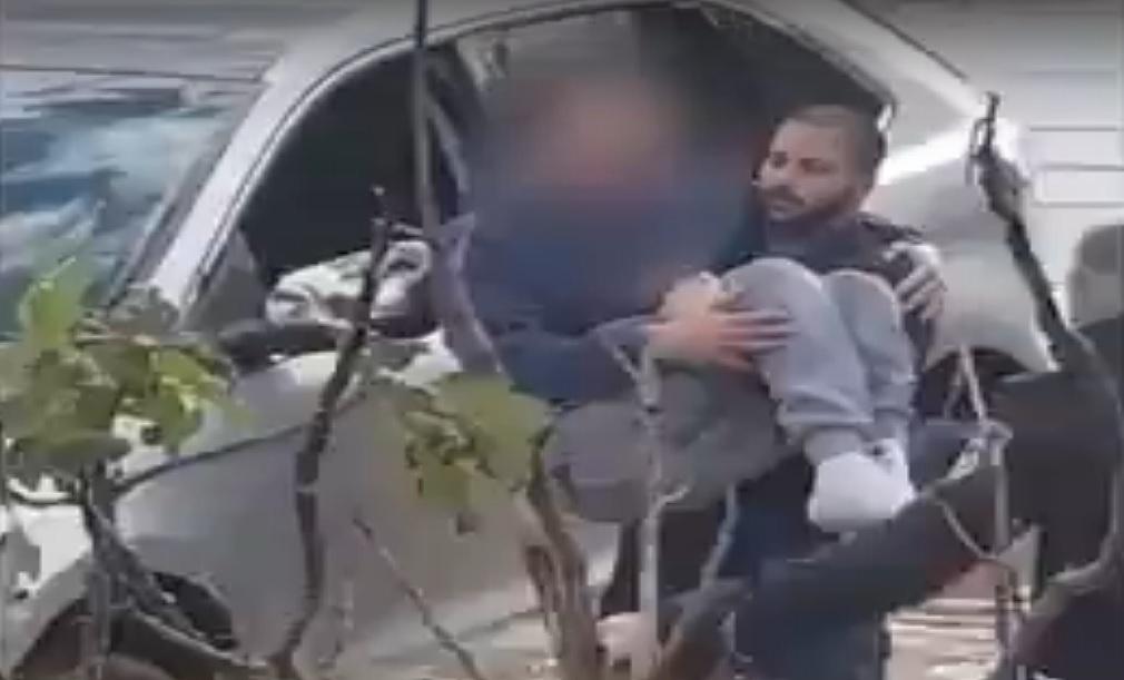 השוטר נושא על ידיו את הנהג הנכה ששקע ומחלץ אותו. צילום: דוברות המשטרה
